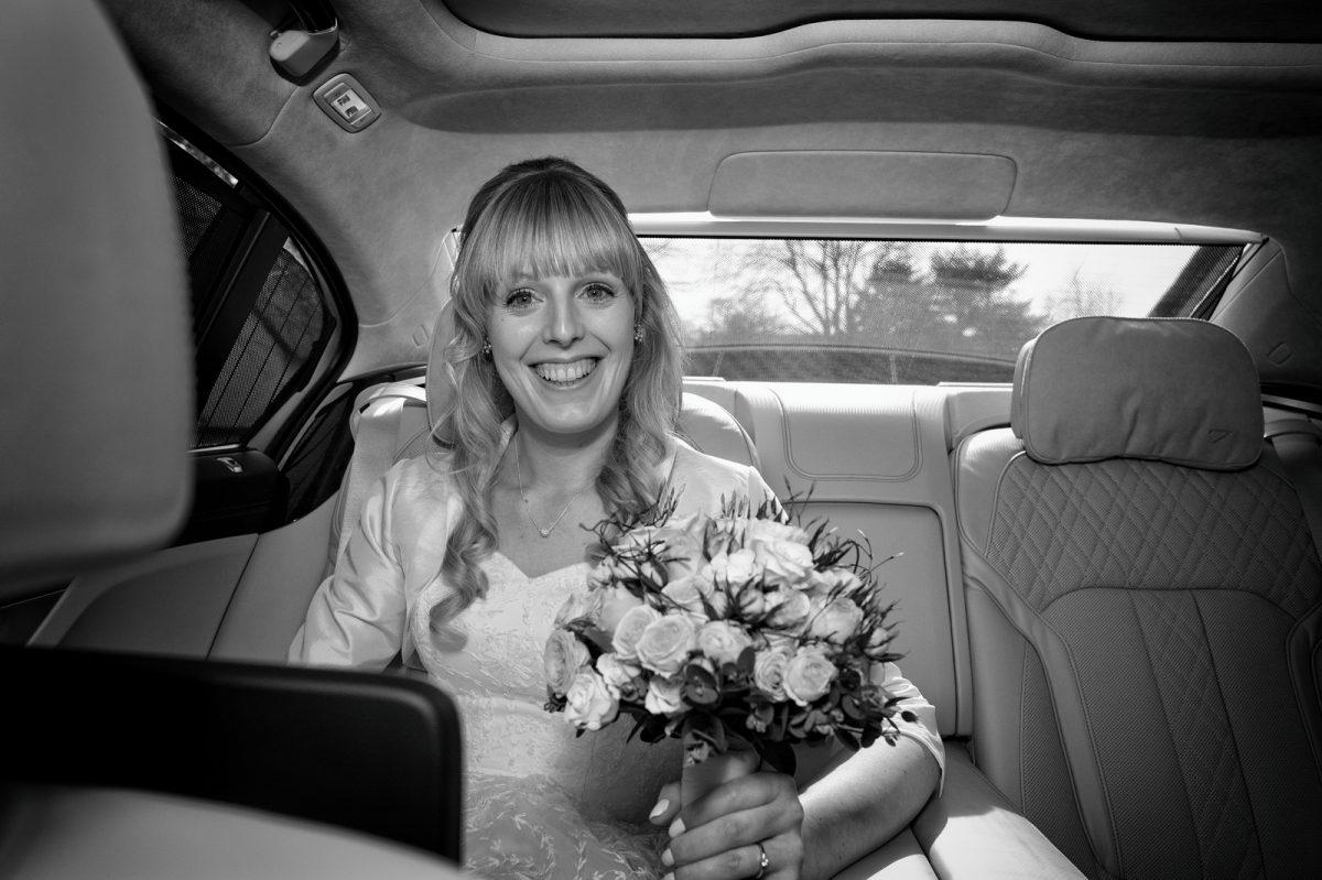 Braut sitzt im Auto und lacht