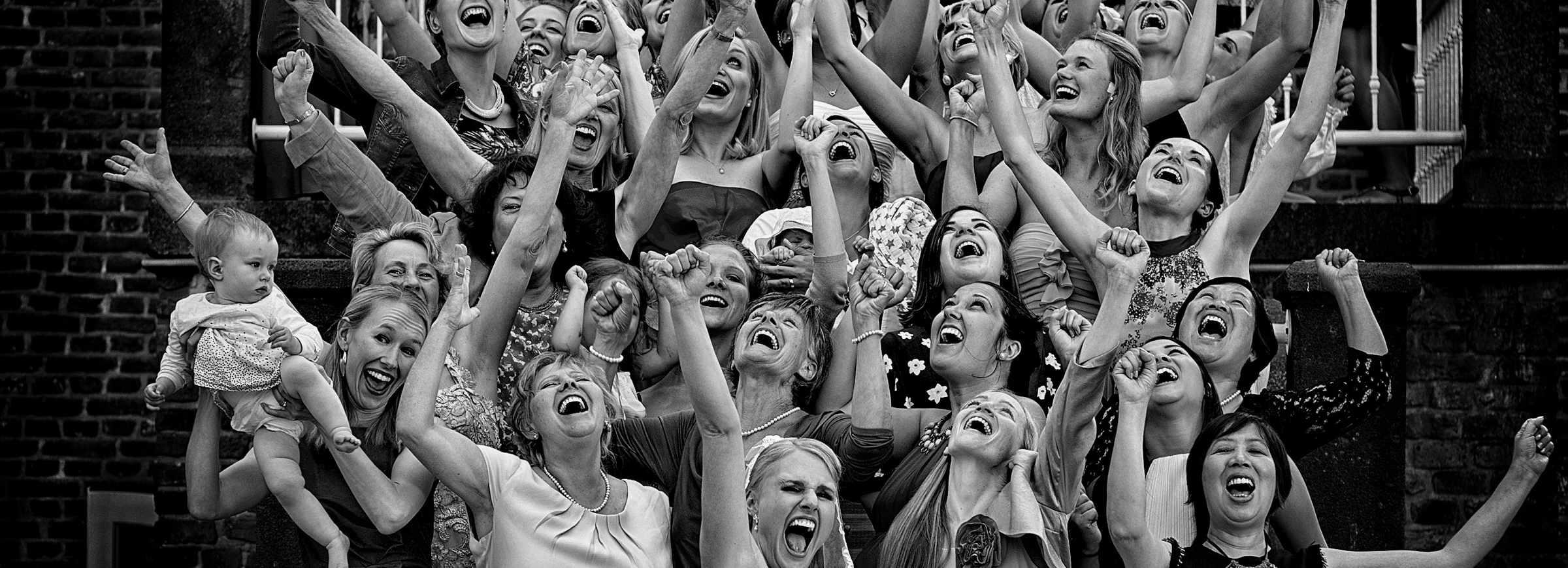 Eine grosse Gruppe an Mädchen und Frauen stehend auf der Treppe und jubelnd!