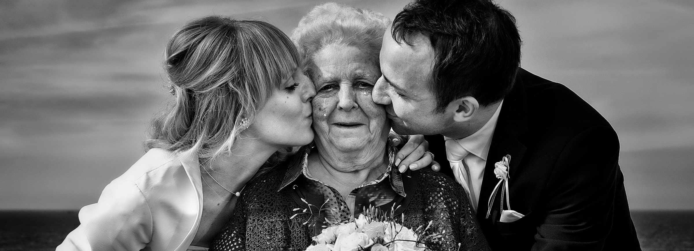 Zur Tränen gerührte Oma steht auf einem Holzsteg in Kampen, das Hochzeitspaar küsst sie von den Seiten auf die Wange. Eine Träne kullert.