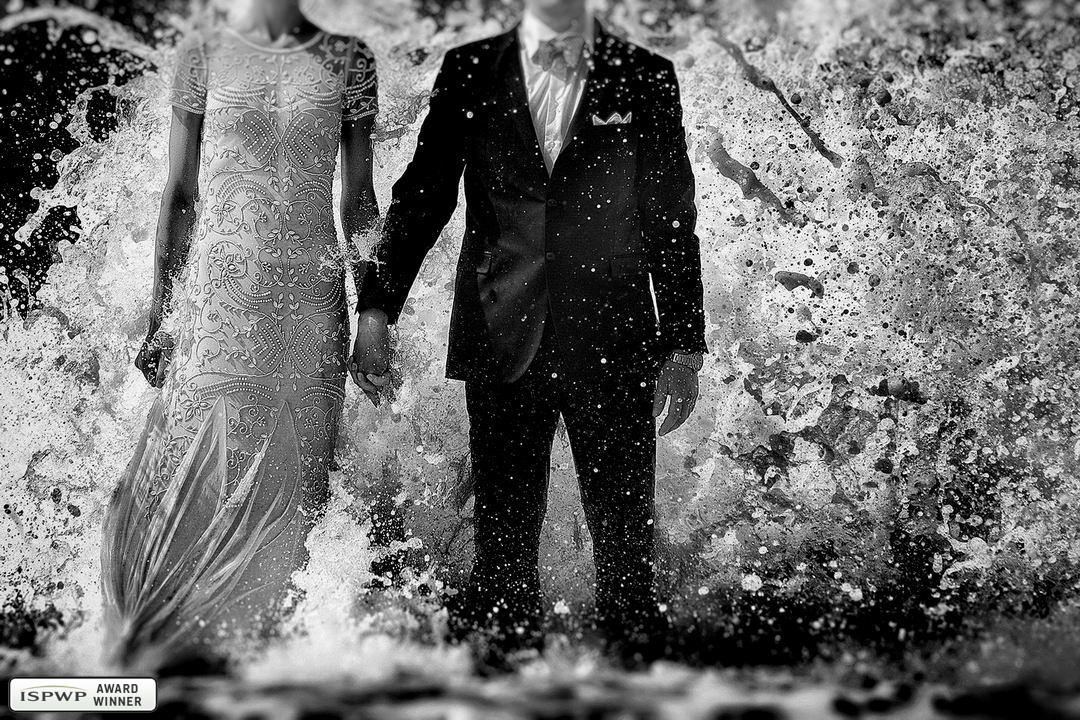 Hochzeit auf Sylt - ein paar steht im Wasser und die Welle kommt