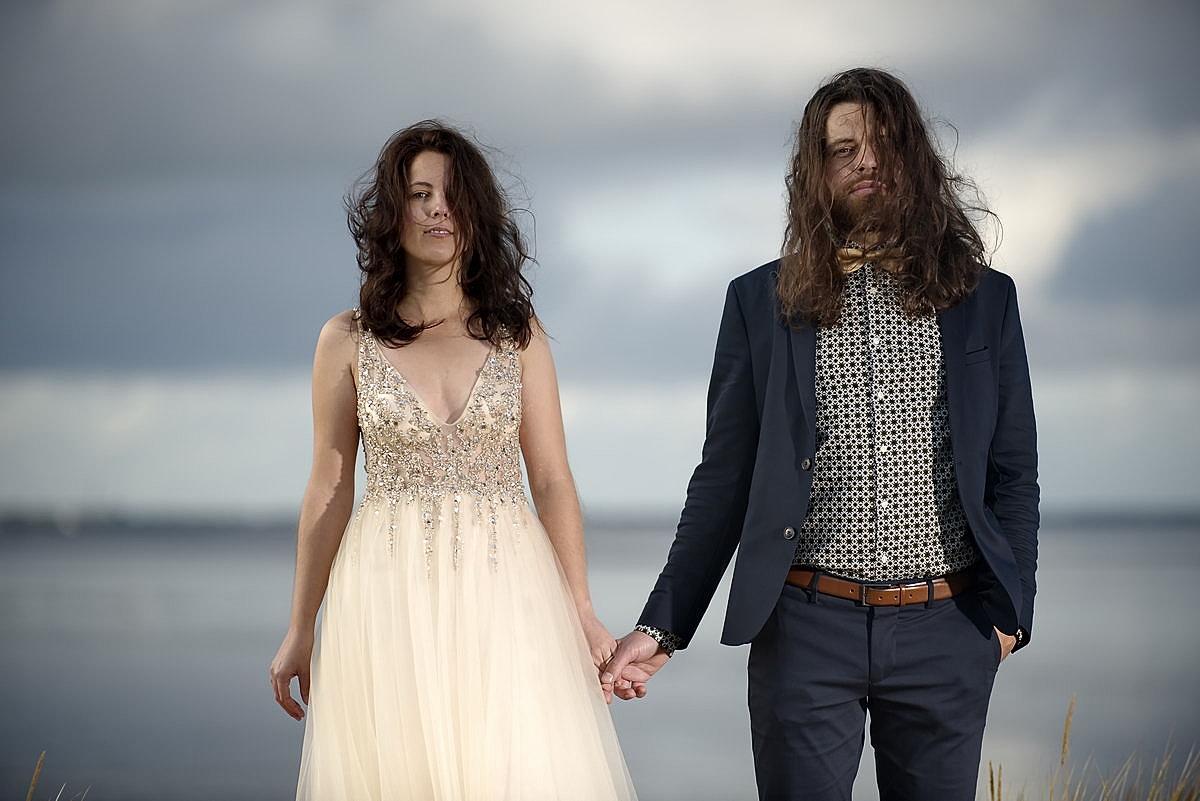 Ein junges Hochzeitspaar hält sich an der Hand. Beide stehen am Watt und schauen in die Kamera
