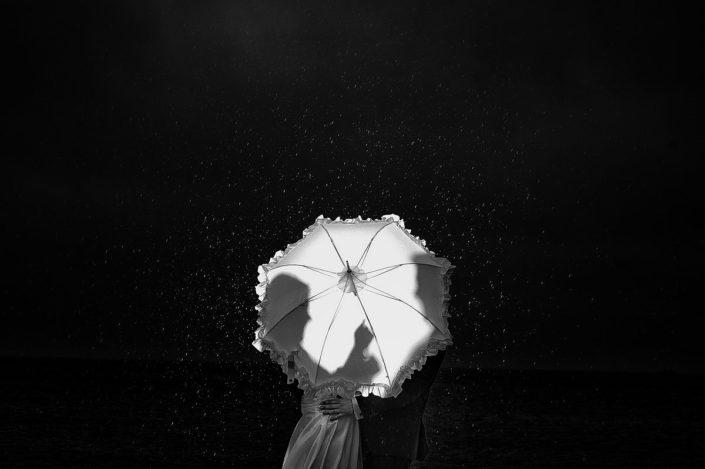 Hochzeitspaar in Regen versteckt hinter Regenschirm