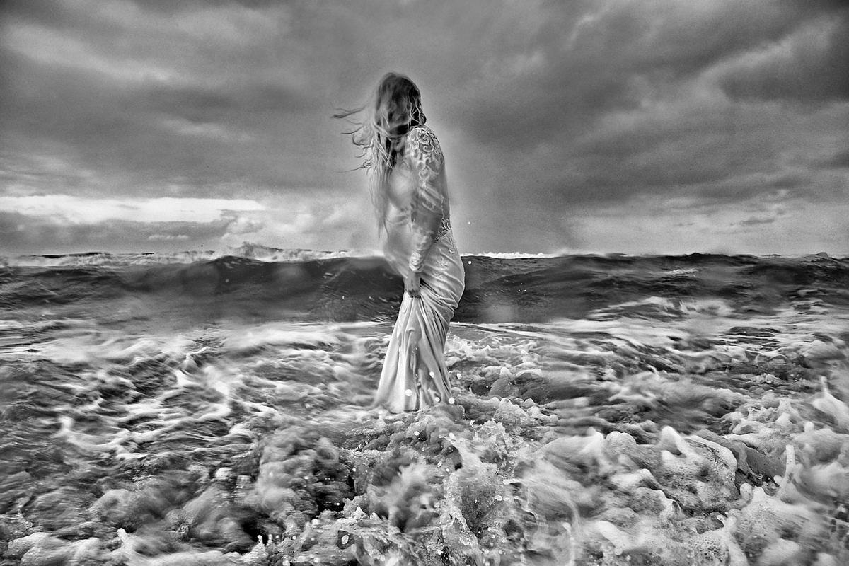 Braut steht voll nass und durchgefroren mitten im Meer auf Sylt