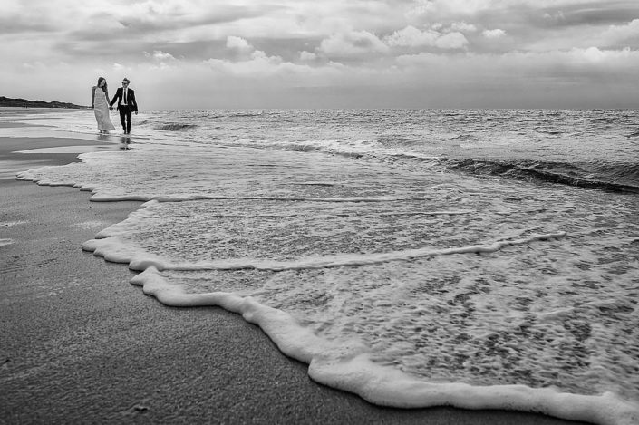 Ein Hochzeitspaar spaziert Hand in Hand und barfuss direkt auf dem Ufer am Strand in Kampen auf Sylt.