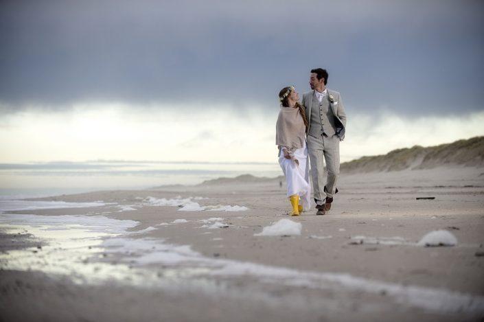 Ein Hochzeitspaar spaziert am Strand von Sylt in herbstlichen kaltem Wetter