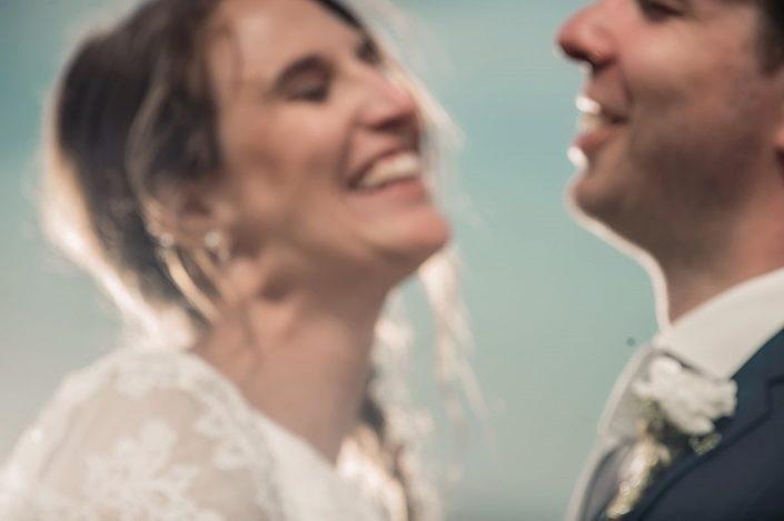 Ein fröhliches Hochzeitspaar noch vor der Corona zusammen lächeln und feiern.