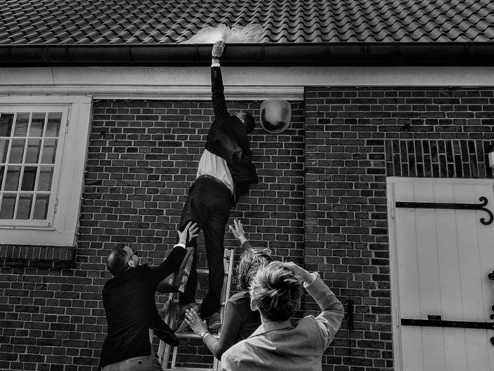 Hochzeitsgäste versuchen zu klettern auf dem Dach der Kirche, nachdem der Wind ein Teil des Hochzeitskleides dort verweht hat.