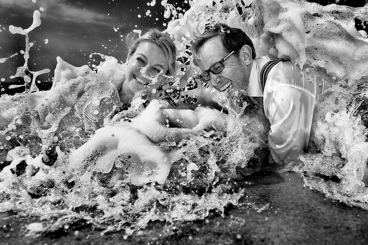 Vollgekleidetes Hochzeitspaar liegt im Wasser am sylter Strand und herzlich lacht, weil die gerade von der Welle getroffen sind und komplett nass sind.