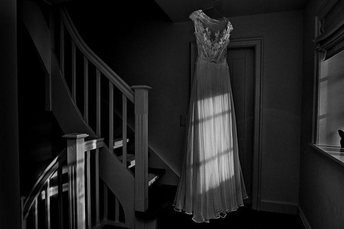 Hochzeitskleid hängt auf dem Bügel in Treppenhaus