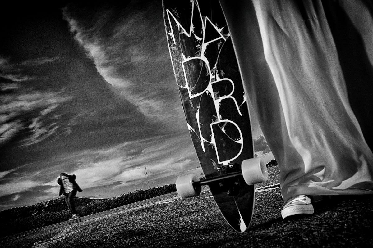 Hochzeitspaar auf Skateboards am Parkplatz