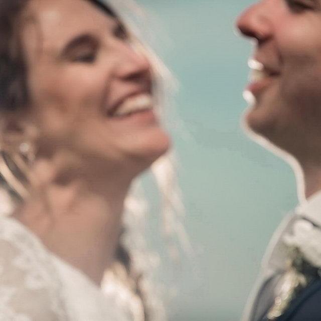 Ein Hochzeitspaar ist nicht ganz in Fokus, man aber sieht, dass die zusammen herzlich lacheln.