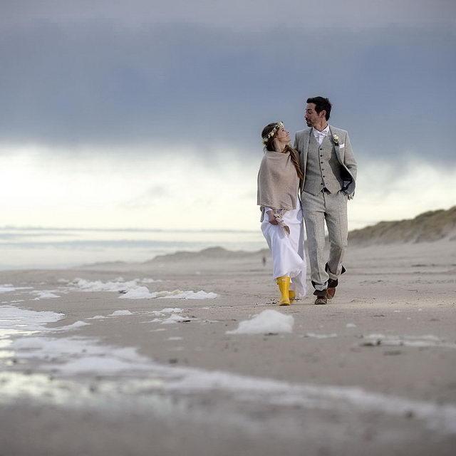 Zwei verliebte schauen sich in die Augen und laufen am herbstlichen Strand Arm in Arm. Offensichtlich handelt es sich um einen Hochzeitspaar, die auf Sylt geheiratet haben.